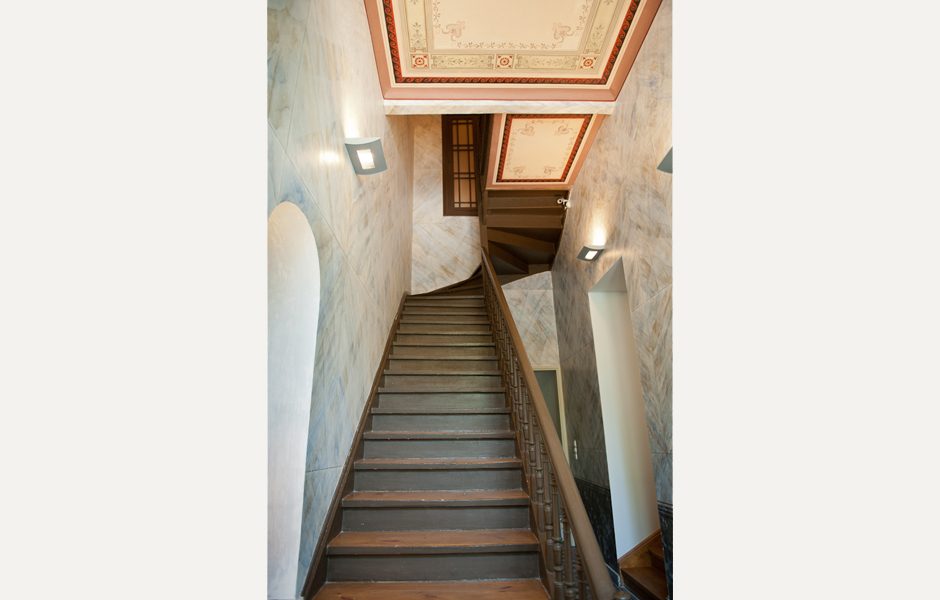 The primary entrance foyer features the original wooden staircase, as well as handpainted faux-marble walls